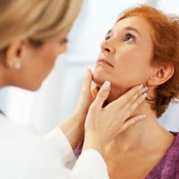 doctor feeling the outside of a woman's throat