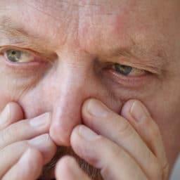 senior man pressing on nose