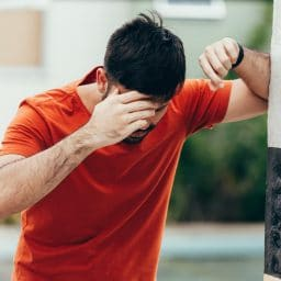 Man puts his hand to his forehead and leans on a pole while experiencing dizziness